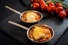 开胃肉用蘑菇,烘烤用在椰子的乳酪,在铁的两个小部分在西红柿附近作为b的一装饰 免版税库存照片