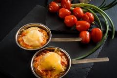 开胃肉用蘑菇,烘烤用在椰子的乳酪,在铁的两个小部分在西红柿附近作为b的一装饰 图库摄影