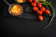 开胃肉用蘑菇,烘烤用在椰子的乳酪,在铁bowlnear西红柿的两个小部分 反对a 免版税图库摄影