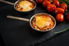 开胃肉用蘑菇,烘烤用在椰子的乳酪,在铁bowlnear西红柿的两个小部分 反对a 库存图片