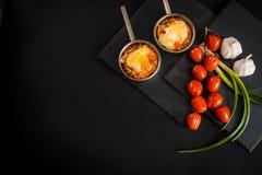 开胃肉用蘑菇,烘烤用在椰子的乳酪,在铁bowlnear西红柿的两个小部分 反对a 免版税库存照片