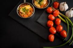 开胃肉用蘑菇,烘烤用在椰子的乳酪,在铁bowlnear西红柿的两个小部分 反对a 库存照片