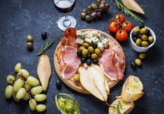 开胃菜、意大利开胃小菜、火腿、橄榄、乳酪、面包、葡萄、梨和杯在石背景的酒 库存图片