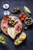 开胃菜、意大利开胃小菜、火腿、橄榄、乳酪、面包、葡萄、梨和杯在石背景的酒 免版税库存图片