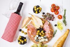 开胃菜、意大利开胃小菜、火腿、橄榄、乳酪、面包、葡萄、梨和酒在白色木背景 库存图片