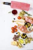 开胃菜、意大利开胃小菜、火腿、橄榄、乳酪、面包、葡萄、梨和酒在白色木背景 免版税库存图片