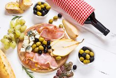开胃菜、意大利开胃小菜、火腿、橄榄、乳酪、面包、葡萄、梨和酒在白色木背景 免版税图库摄影