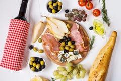 开胃菜、意大利开胃小菜、火腿、橄榄、乳酪、面包、葡萄、梨和酒在白色木背景 库存照片