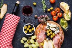 开胃菜、意大利开胃小菜、火腿、橄榄、乳酪、面包、葡萄、梨和酒在石背景 图库摄影
