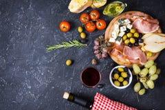 开胃菜、意大利开胃小菜、火腿、橄榄、乳酪、面包、葡萄、梨和酒在黑暗的石背景 顶视图 库存图片
