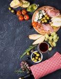 开胃菜、意大利开胃小菜、火腿、橄榄、乳酪、面包、葡萄、梨和酒在黑暗的石背景 顶视图 免版税库存图片