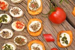 开胃菜乳酪和bruschetta用草本、蕃茄和辣椒 免版税图库摄影