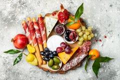开胃菜制表与开胃小菜快餐 乳酪和肉品种上在灰色具体背景 顶视图,平的位置 图库摄影