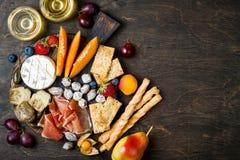 开胃菜制表与意大利开胃小菜快餐和酒在玻璃 乳酪和熟食店品种上在土气木桌 免版税图库摄影