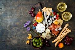 开胃菜制表与意大利开胃小菜快餐和酒在玻璃 乳酪和熟食店品种上在土气木桌 库存照片