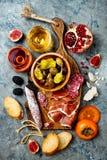 开胃菜制表与意大利开胃小菜快餐和酒在玻璃 在灰色具体背景的熟食店委员会 免版税库存图片