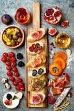 开胃菜制表与意大利开胃小菜快餐和酒在玻璃 被设置的Brushetta或地道传统西班牙塔帕纤维布 库存图片