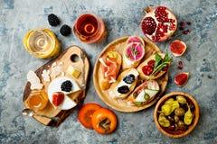 开胃菜制表与意大利开胃小菜快餐和酒在玻璃 被设置的Brushetta或地道传统西班牙塔帕纤维布 库存照片