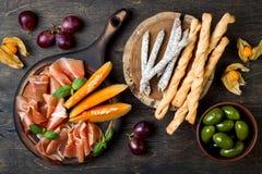 开胃菜制表与意大利开胃小菜快餐 乳酪和熟食店品种上在土气木背景 图库摄影