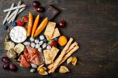 开胃菜制表与意大利开胃小菜快餐 乳酪和熟食店品种上在土气木背景 免版税图库摄影