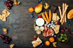 开胃菜制表与意大利开胃小菜快餐 乳酪和熟食店品种上在土气木背景 免版税库存图片