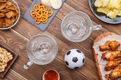 开胃菜和啤酒在桌上手表的足球比赛 图库摄影