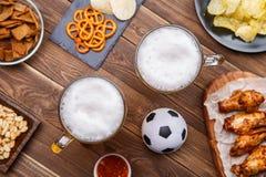开胃菜和啤酒在桌上手表的足球比赛 库存照片