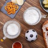 开胃菜和啤酒在桌上手表的足球比赛 免版税图库摄影