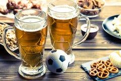 开胃菜和啤酒在桌上手表的足球比赛 免版税库存图片