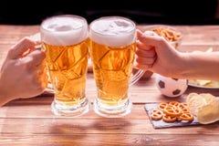 开胃菜和啤酒在桌上手表的足球比赛 免版税库存照片