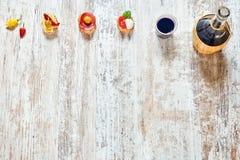 开胃菜和红葡萄酒的混合在一张木桌上 免版税库存照片