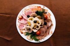 开胃菜在餐馆切了在一个盛肉盘的肉在桌上 图库摄影