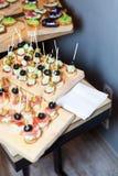 开胃菜木盘子在板台咖啡桌上的在与jamon、黄油奶油和橄榄的宴会 选择聚焦 免版税库存照片
