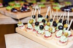 开胃菜木盘子在板台咖啡桌上的在与jamon、黄油奶油和橄榄的宴会 选择聚焦 库存图片