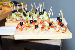 开胃菜木盘子在板台咖啡桌上的在与jamon、黄油奶油和橄榄的宴会 库存图片