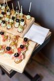 开胃菜木盘子在板台咖啡桌上的在与jamon、黄油奶油和橄榄的宴会 免版税图库摄影