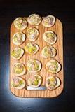 开胃菜木盘子在板台咖啡桌上的在宴会用烟肉、绿色草本和橄榄 库存照片