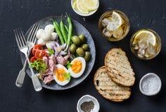开胃菜桌-罐装金枪鱼,青豆,无盐干酪乳酪,蕃茄板材,煮沸了鸡蛋、橄榄、烤面包和两glasse 免版税图库摄影