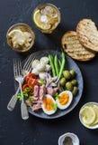 开胃菜桌-罐装金枪鱼,青豆,无盐干酪乳酪,蕃茄板材,煮沸了鸡蛋、橄榄、烤面包和两glasse 库存图片