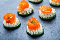 开胃菜点心用在石板岩背景关闭的三文鱼,黄瓜和乳脂干酪 免版税库存图片