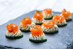 开胃菜点心用在石板岩背景关闭的三文鱼,黄瓜和乳脂干酪 库存照片