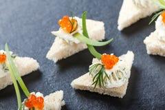 开胃菜点心用在石板岩背景关闭的红色鱼子酱和乳脂干酪 库存照片