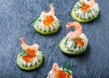 开胃菜点心用在石板岩背景关闭的红色鱼子酱,虾和乳脂干酪 库存照片