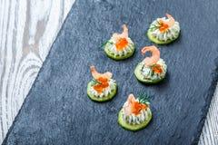 开胃菜点心用在石板岩背景关闭的红色鱼子酱,虾和乳脂干酪 图库摄影