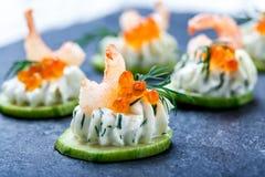 开胃菜点心用在石板岩背景关闭的红色鱼子酱,虾和乳脂干酪 库存图片