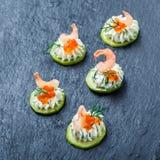 开胃菜点心用在石板岩背景关闭的红色鱼子酱,虾和乳脂干酪 免版税库存照片