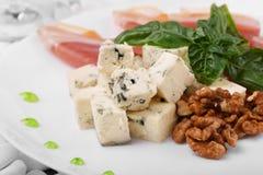 开胃菜特写镜头  羊乳干酪乳酪 滋补核桃 菠菜和火腿 在白色板材背景的成份 免版税库存图片