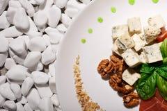 开胃菜特写镜头  羊乳干酪乳酪 滋补核桃 菠菜和火腿 在白色的成份晃动背景 免版税库存图片