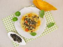 开胃菜用小米、红色kuri南瓜和南瓜籽 免版税图库摄影