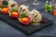 开胃菜用有壳的面包、bresaola、乳酪和卵黄质在石背景 图库摄影